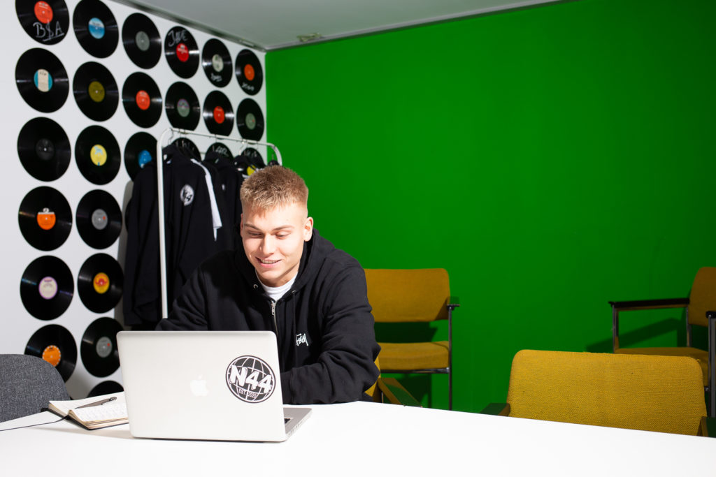 Lucs Goerdel sitzt an seinem Laptop. Hinter ihm ein Greenscreen.